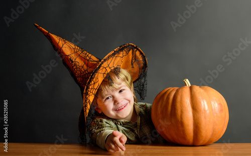 Preparation Halloween holiday. Cute boy in witch hat with halloween pumpkin pointing to you. Happy Halloween. Kid trick or treat. Halloween party. Boy dressed up trick or treating. Child with pumpkin.