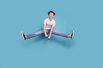 Full length body size photo of boy having done splits rights in air while isolated with blue background Fototapete