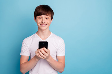 Photo of tight smiling boy taking smartphone with his own hands for first time while isolated with blue background