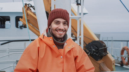 Portrait of Dressed in Bright Protective Coat Smiling on Camera Fisherman on Commercial Fishing Boat.