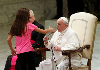 Pope Francis allows a little girl suffering from an undisclosed illness to move around undisturbed clapping and dancing on the stage for most of his general audience in Paul VI Hall at the Vatican