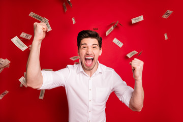 Photo of successful champion winning man standing in rain of currency bucks banknotes while isolated with red background