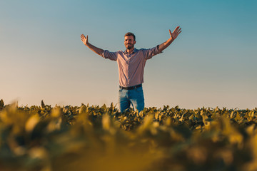 Portrait of farmer standing in soybean field at sunset with his arms outstretched.