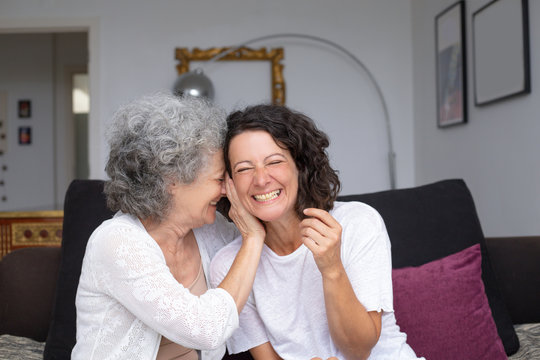 Happy mother and daughter laughing together. Cheerful senior mother and adult daughter sitting on couch and laughing at home. Relationship concept