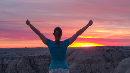 CLOSE UP: Cheerful young woman on top of the mountain celebrating at pink sunset
