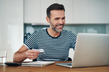 Picture of smiling man using laptop and credit card to do online shopping