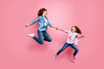 Photo of foxy little lady and her excited mom jumping high walking toy shop wear casual jeans outfit isolated pink background Wall mural