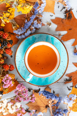 composition still life of a mug with hot leaf tea with berries and autumn leaves on a wooden surface