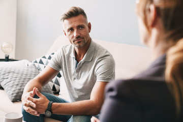 Photo of confident focused man having conversation with psychologist in room