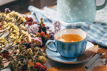 Foto op Aluminium Thee autumn warming tea on a wooden table with autumn tree leaves lying nearby