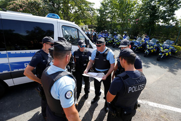French Gendarmes and German police look at a map at a toll station in Anglet ahead of the G7 Summit in the French coastal resort of Biarritz