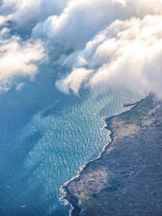 View from plane window. Aerial top view of sea, sky, clouds and ground.