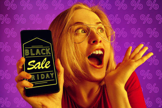 Portrait of young caucasian woman showing mobile phone screen on purple background with percents. Concept of sales, black friday, cyber monday, finance, business. Online shops and payments bill.