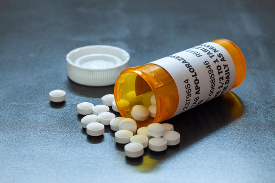 Prescription bottle with backlit Lorezapam tablets. Lorezapam is a generic prescription anti-anxiety medication.