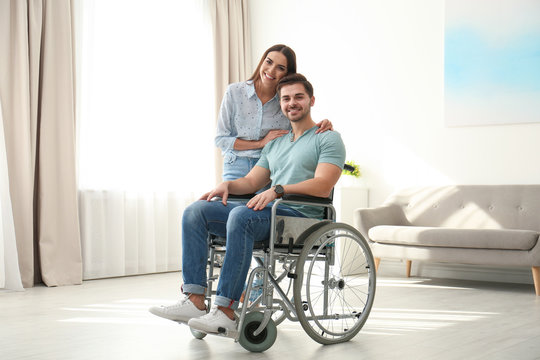 Young woman with man in wheelchair indoors