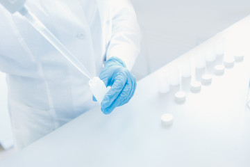 Scientist in white coat takes analysis from paragraph with pipette. Chemistry biological background...