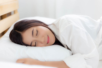 Charming beautiful woman is lying down on her bed at bedroom. Glamour woman has good sleep all night on bed with smiley face. Attractive beautiful girl has beautiful face with white pajamas Wall mural