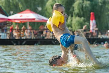 father throwing son in water having fun