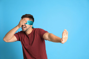 Young man with blindfold on blue background