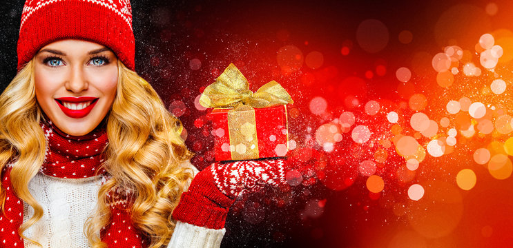 Smiling and happy blond woman with christmas gift box on red background. Girl celebrates New Year 2020 in winter. Shopping black friday sale concept for shop.