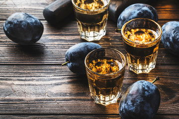 In de dag Alcohol Slivovica - plum brandy or plum vodka, hard liquor, strong drink in glasses on old wooden table, fresh plums, copy space
