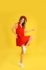 Beautiful young woman in red dress dancing on yellow background