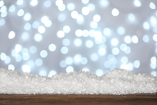Heap of snow on wooden surface against blurred background. Christmas season