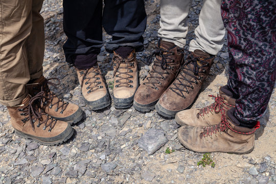 Company four tourists only legs together in brown trekking hiking boots with laces on rocky cliff. Concept freedom, travel lifestyle adventure vacations, traveler outdoor wild nature summer steps
