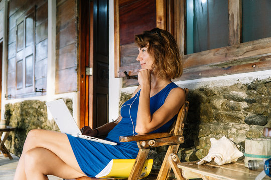 Attractive woman sitting on a chair working with her laptop outside the cabin.
