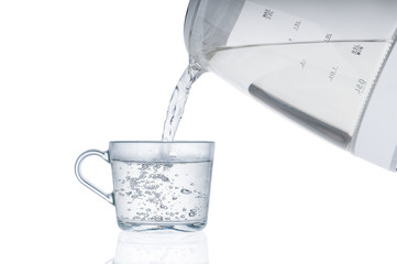 Pouring hot water from an electric kettle in cup isolated on white background
