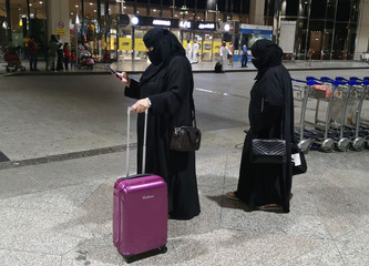 Saudi women walk with their luggages as they arrive at King Fahd International Airport in Dammam
