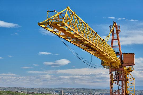 Yellow construction jib crane tower against blue sky