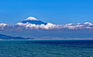 Sea approach to Shimizu, Japan with the snow capped peak of the iconic Mt. Fuji gleaming above low clouds