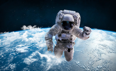 Spoed Foto op Canvas Nasa Astronaut in the outer space over the planet Earth. Clouds on background. Spaceman. Elements of this image furnished by NASA