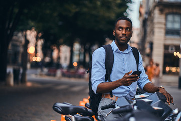 Young attractive student is renting bike and is making web payment using his mobile phone.