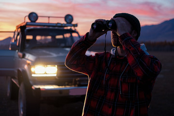 A man with binoculars near the car at sunset. Man Binoculars Looking Mountain Cloudscape Traveling Concept
