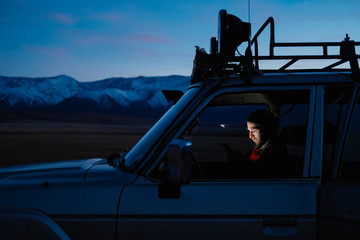 night fell, and the traveler guy sits in the car and watches the way to home