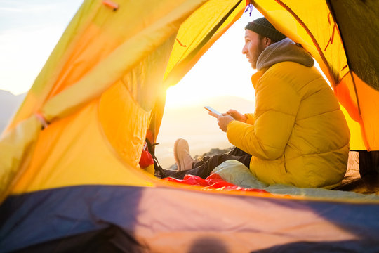 the guy in the yellow jacket sits in a tent and enjoys the view of nature and the mountains