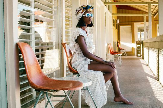 Young Fashionable Black Woman Sitting on Veranda of Stylish Minimalist Hotel