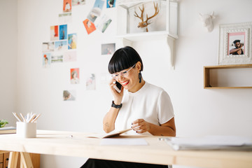 Cheerful trendy woman speaking on phone in office