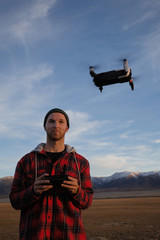 Guy traveler in a plaid jacket controls the drone