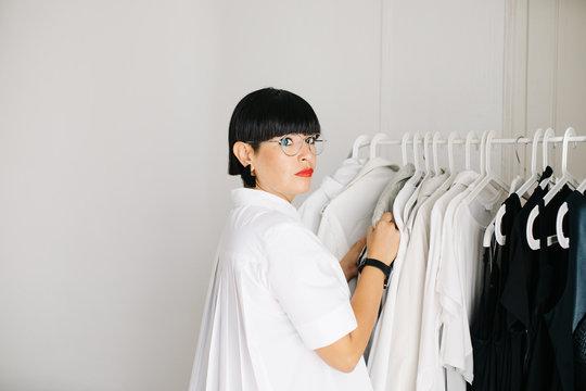 Stylish designer exploring clothes on rack