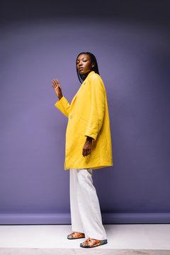 Modern black woman in yellow jacket on purple background