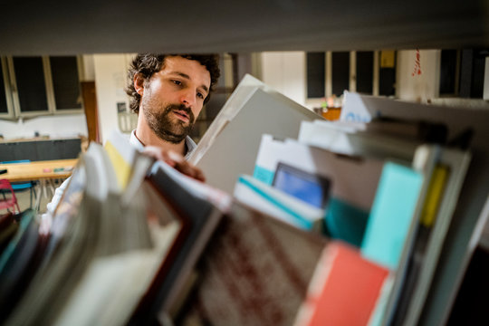 Businessman reading file at shelf in office