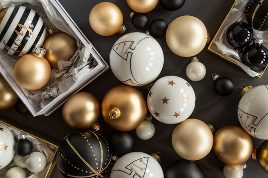 Black, white and gold Christmas ornaments on grey background
