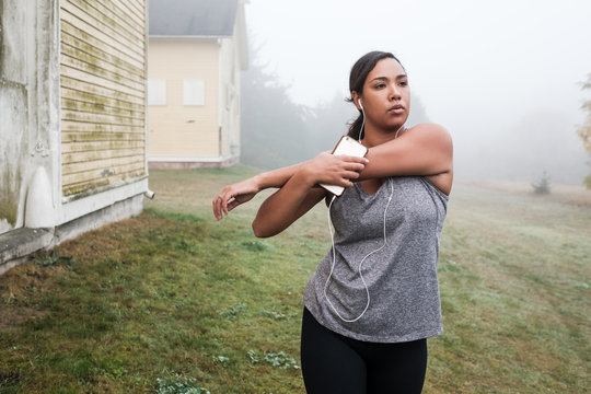Beautiful Mixed Race Woman Stretching Before Exercising