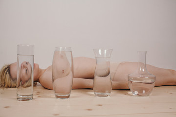 Woman lying on back behind water in vases