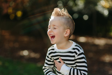 Cute young boy in a mohawk laughing