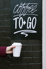 Hand holding white paper cup with coffee.