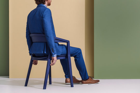 Rear view of man in blue suit sitting in a chair